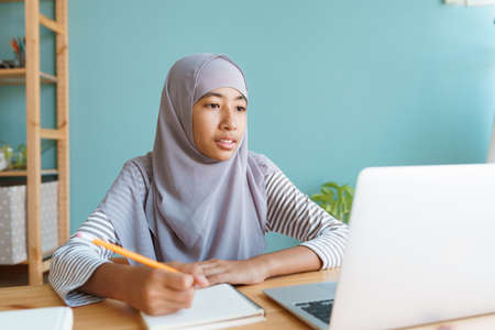Muslim girl learning online via the internet tutor on a laptop computer, Asia child is studying while sitting Interior at home morning. Concept of online learning at home Stock fotó