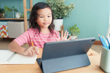 Asian little girl waving in greeting online tutor on tablet digital in interior at home morning. Concept of online learning at home