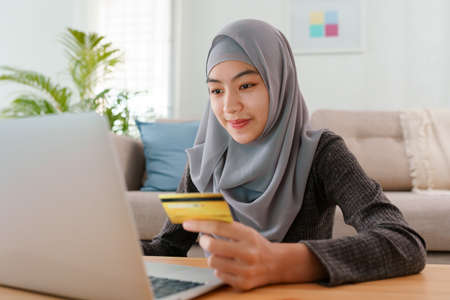 Muslim young women wear hijab are buying online with a credit card while sitting living room at home. Beautiful woman is using computer laptop and doing online transactions