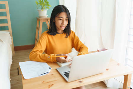 Asian woman learning online with a tutor via the internet with a laptop, Asia student girl video conference on a computer on a desk, Concept online learning at home