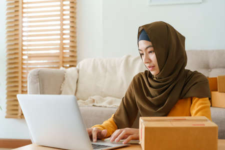 Muslim young women wear hijab using typing and checking order the customer address on the computer laptop at home morning. Concept business small and shop online
