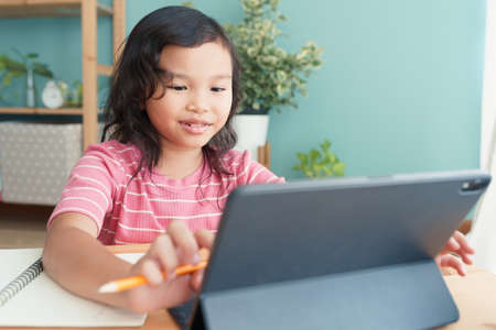 Happy Asian little girl learning online with a tutor via the internet on a tablet digital at home morning, Concept online learning at home Stock fotó