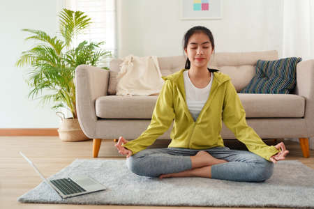 Beautiful of young women Practicing yoga online with Trainer  learning  computer laptop on a yoga mat  at home morning, Concept of relaxation and meditation Stock fotó