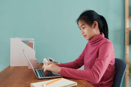 Asian student Wear long sleeves pink online learning via the internet on a laptop computer at home morning.  Concept of online learning at home