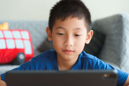 Asian boy handsome studying online via internet on a tablet with a tutor, Close-up of man face. Concept of online learning at home