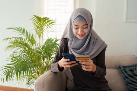 Muslim young women wear hijab are buying online with a credit card while sitting on a sofa. Beautiful teenager is using a smartphone and doing online transactions