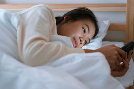 Asian woman using a smartphone while lying in the bedroom at the night