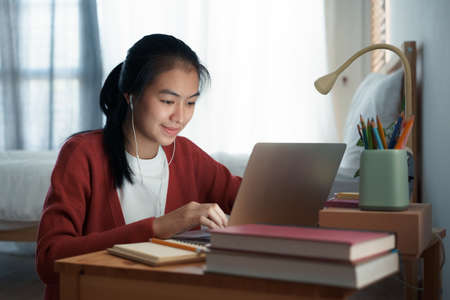 Asian woman video call online via the internet tutor on a computer laptop with headphone, Asia girl is studying while sitting in the bedroom at night. Concept online learning at home