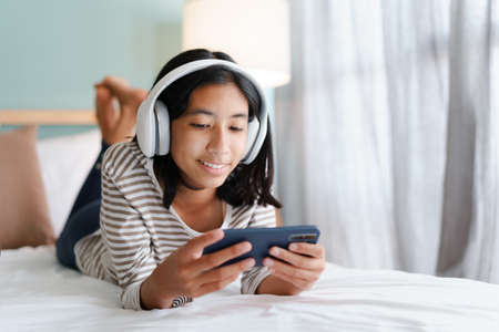 Asian girl using a smartphone with headphones while on the bed in the morning. Stock fotó