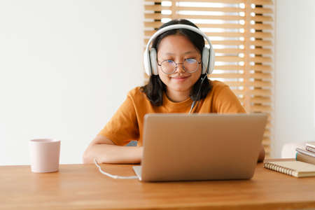 Asian student woman learning online using a computer laptop with headphones while sitting workplace on a table at home in the morning. Concept online learning at home Stock fotó