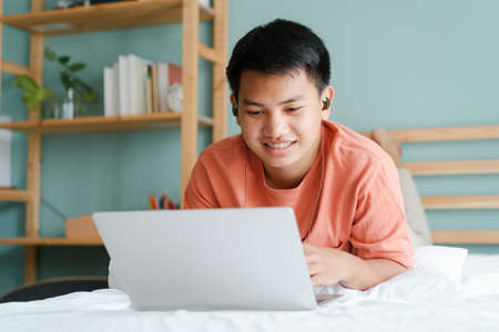 Asian student man learning online using a computer laptop with headphones while lying on bed at home in the morning. Concept online learning at home