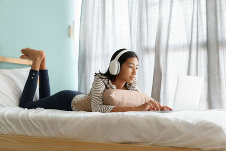 Asian girl using a laptop with Headphones while lying on the bed at home morning and sunlight, happy Asia smile on face women