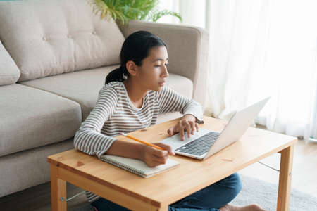Asian girl learning online via the internet tutor on a laptop computer, Asia child is studying while sitting in living room at home morning. Concept of online learning at home
