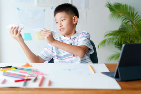 asian boy playing paper airplane while sitting at home morning, asia men  learning online with teacher on tablet