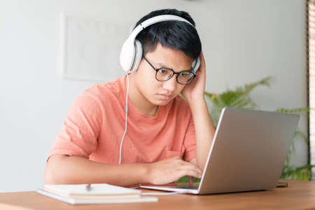 Asian student man learning online using a computer laptop with headphones while sitting workplace on a table at home in the morning. Concept online learning at home