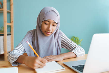 Muslim girl learning online via the internet tutor on a laptop computer, Asia child is studying while sitting Interior at home morning. Concept of online learning at home Standard-Bild
