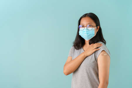 Asian women wearing face mask vaccinated Showing arm bandage to protect  spread on blue background.