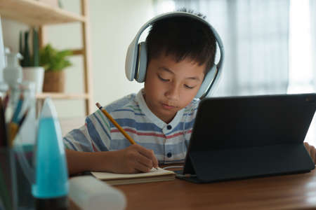 Asian boy learning online via internet with a tutor on a tablet digital with headphone, Asia child is studying while sitting in the living room at home. Concept of online learning at home Standard-Bild