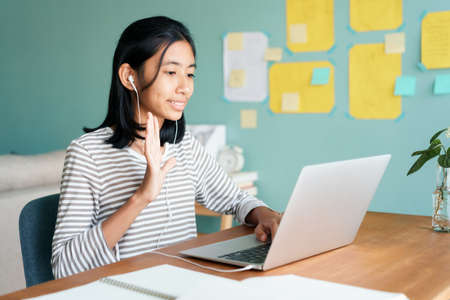 Happy Asian girl waving in greeting online tutor on tablet with headphones while sitting on workplace at home morning, Concept online learning at home