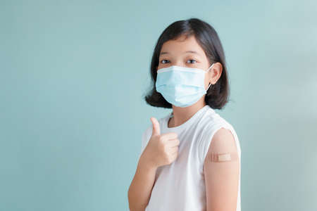 Asian little girl wearing face mask vaccinated Gesturing Thumbs Up  Showing arm bandage to protect spread on blue background