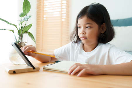 Asian little girl do homework and learning online via the internet tutor on a smartphone, Concept of online learning at home