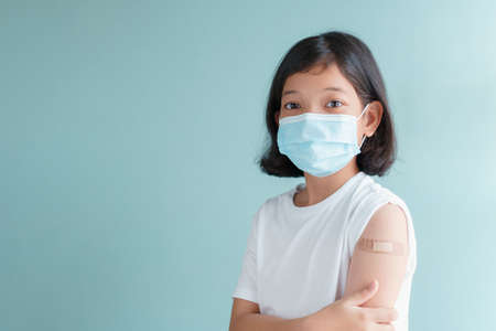 Asian little girl wearing facemask vaccinated Showing arm bandage to protect spread on blue background Standard-Bild
