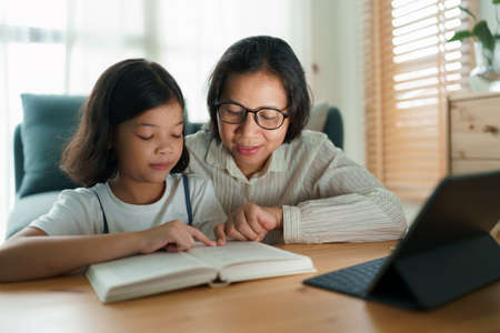 Asian family with daughter doing homework and read a book by using tablet with mother help. Concept of online learning at home. Close up of face women
