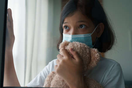 Asian little girl wearing medical protective face mask, asia child looking outside window with teddy bear, sadness, lonely, self isolation stay to global pandemic Standard-Bild
