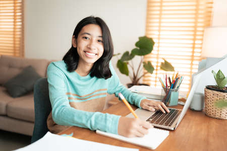 Happy Asian girl smile on the face, Asia student learning online on laptop at home. Portrait of women looking to camera