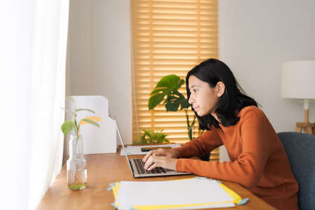 Asian girl student learning online via the internet with tutor on laptop, asian woman typing work on a computer, Concept online learning at home Standard-Bild