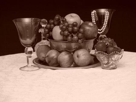 sepia toned image of fresh fruit in brass bowl surrounded by goblets with a string of pearls photo