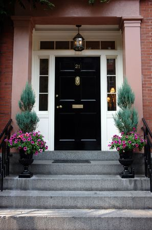 elaborate: Black door in Boston on a stately brownstone in the beacon hill area. Ornate flower urns and elaborate door knocker. Lights on inside the house can be seen from the street.