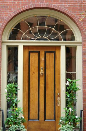Natural woodgrain door with black trim, brass number and door knocker and handle, arched window above doorway with fancy curved panes of glass, flower boxes on either side of door which is flanked by windows, it is a brick home in the beacon hill area of
