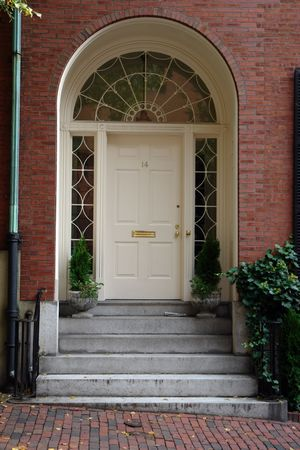 A white arched doorway in the historice section of boston called beacon hill, the arched window above the door looks like a spider web, and half circle panes adorn the sides of the door.