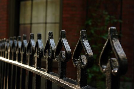 bowed: Black shiny wrought iron fence with tops shaped like spades, shallow depth of field to add a spooky feel to the image, brick building with window in the background.