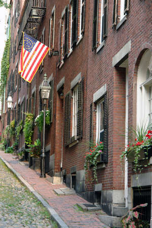 Walking up the cobblestone alley called Acorn Street lined with brick buildings, brick sidewalks old gas lanterns wooden shutters, flower boxes and an early american flag