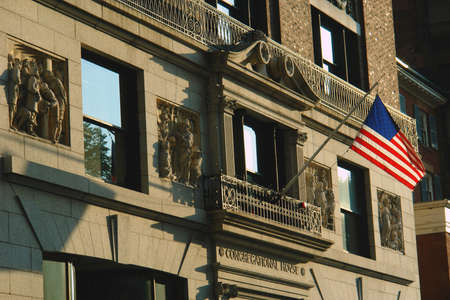 congregational: close up of the front of the building on beacon street in boston that was used in the television show Ally McBeal. Here we see the detail in the carvings and the American flag. Congregational House
