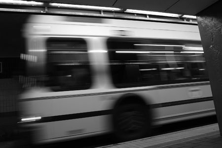 black and white image of bus in motion leaving station photo