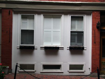 a row of three white windows with shutters on the first floor of a red brick building photo