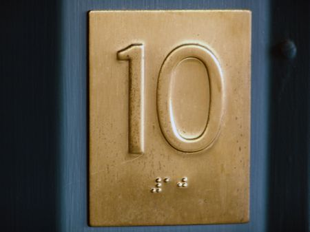 a golden colored number ten with ten written in braille beneath it