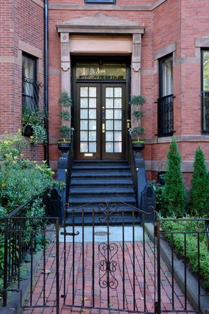 new entry: Brown french double doors sitting stately atop of black painted stairs behind an iron gate