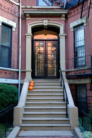 Brown french double doors sitting stately atop of cement stairs adorned with pumpkins