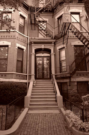 shows entryway, brick sidewalk, fire escape, pumpkins, gates and more in this timeless image of boston photo