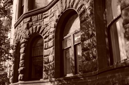 arched windows in curved stone building looking very castle like, boston massachusetts, sepia photo