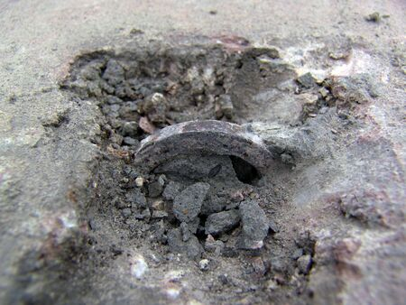 broken cement revealing an iron ring