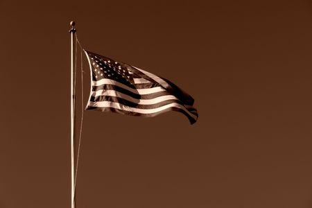 american flag blowing in the breeze high atop a flag pole, sepia