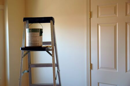 ladder with paint can and brush in freshly painted room, lit by sun and showing a door