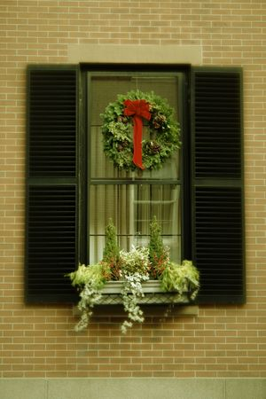 antiqued: christmas wreath hanging in window of brick apartment building with flower box below, antiqued colors