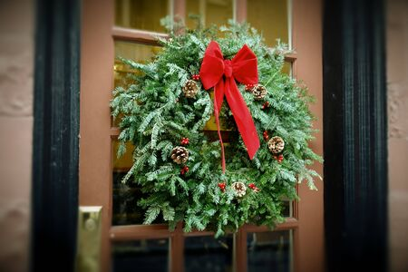 christmas wreath hanging in window of brick apartment building with flower box below, antiqued colors
