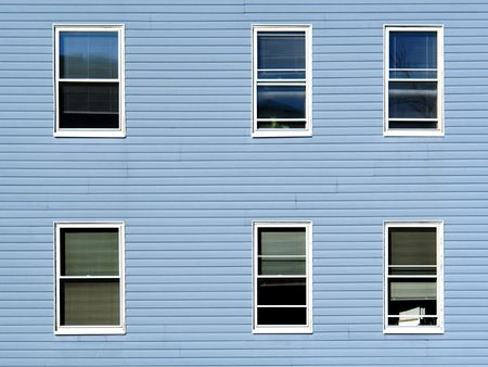 six windows on an apartment building in the sunshine, the building is covered in blue vinyl siding